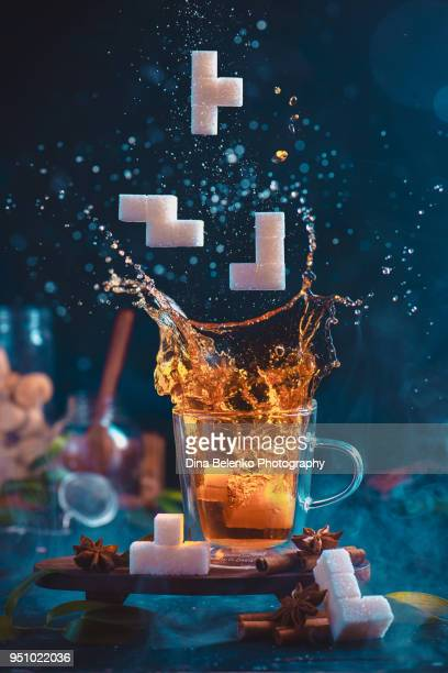 Splash of tea in a double wall glass with sugar Tetris pieces. 8-bit video game in real life concept with copy space. Creative action food photography.