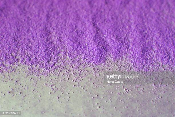 Splashes of purple powder paint on a purple background
