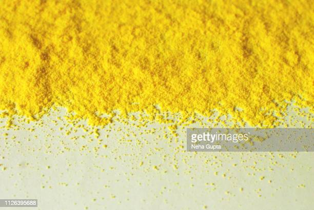 Splashes of yellow powder paint on a half-white background