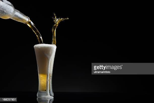 Spritzendes Wasser-Bier gießen in Glas
