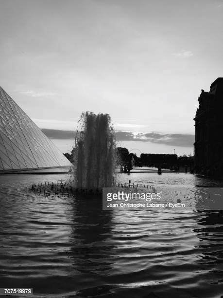 Splashing Fountain In Pond At Musee Du Louvre Against Sky