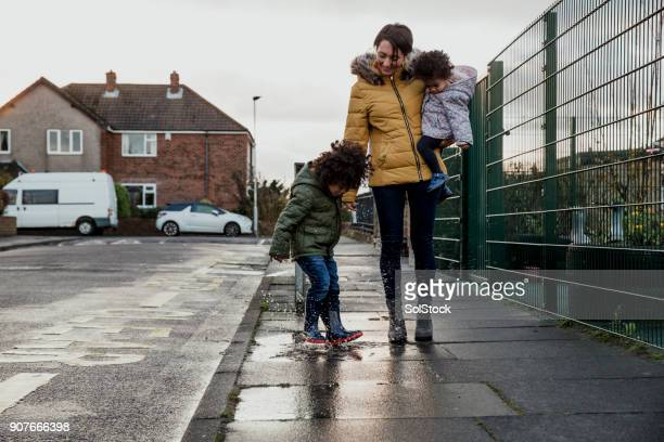 splashing in a puddle - single mother stock photos and pictures