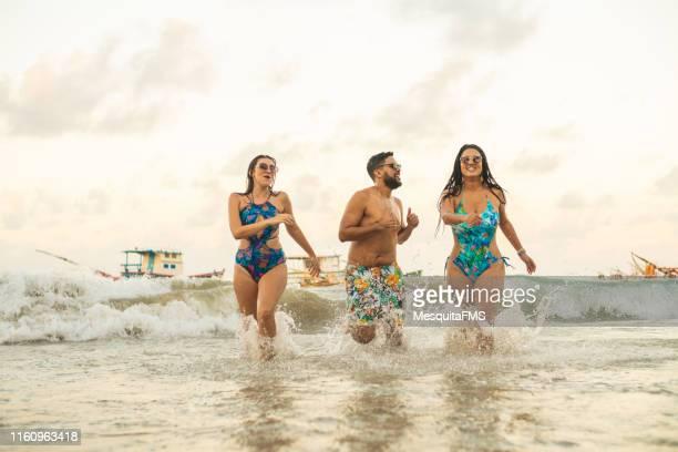 splashing in the waves of porto de galinhas beach - porto galinhas stock photos and pictures