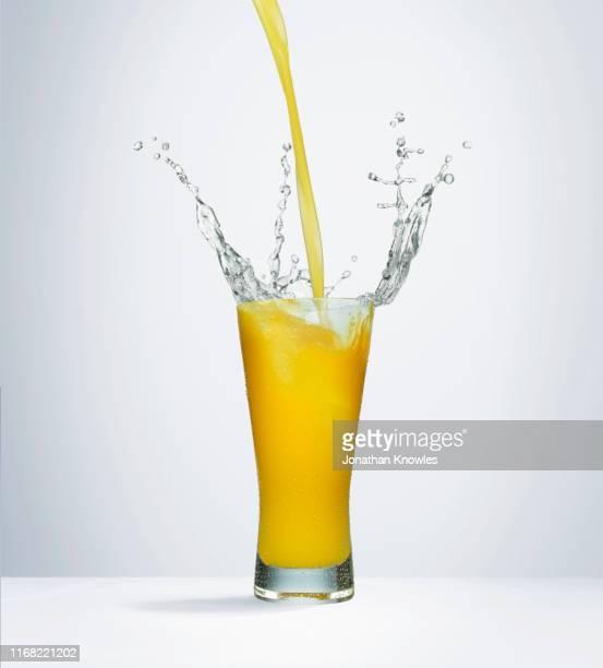 splashing orange juice - cold drink stock pictures, royalty-free photos & images