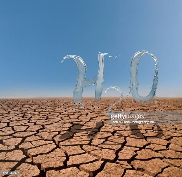 Splashing water forming H2O in desert landscape