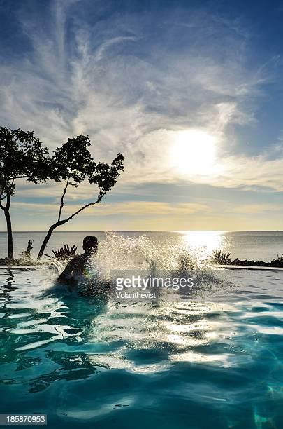 Splashing water from pool at sunset w/ sea back