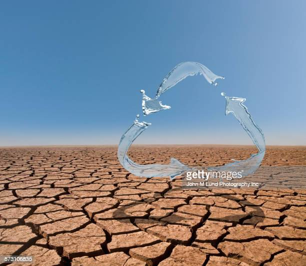 splashing water in recycling symbol over dry desert landscape - scarce stock pictures, royalty-free photos & images