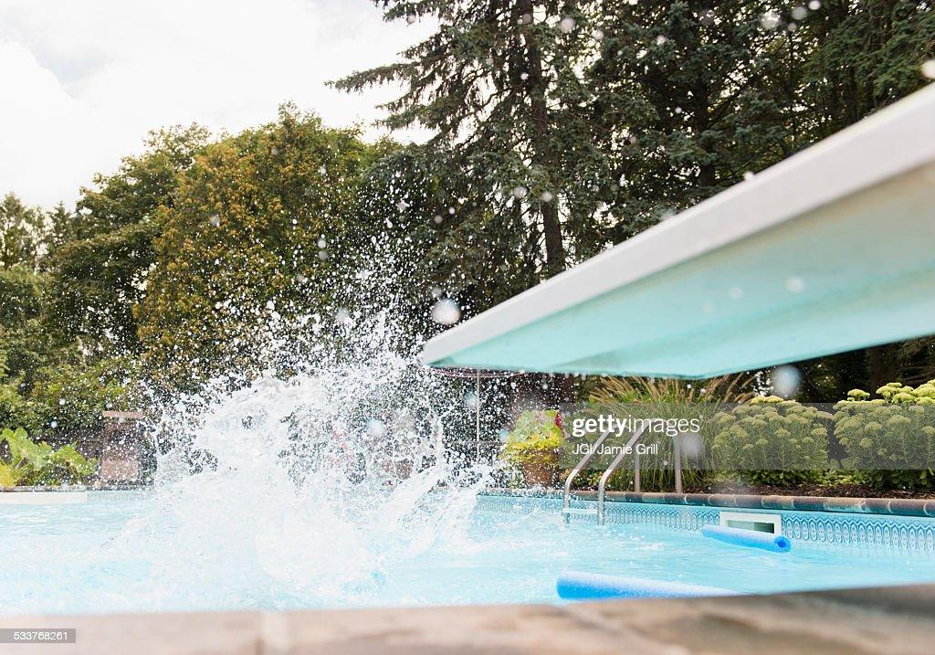 Splashing water near diving board in swimming pool : Foto stock