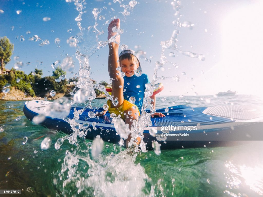 Photo of a little boy being playful and splashing in the sea, while sitting on a stand-up paddle board
