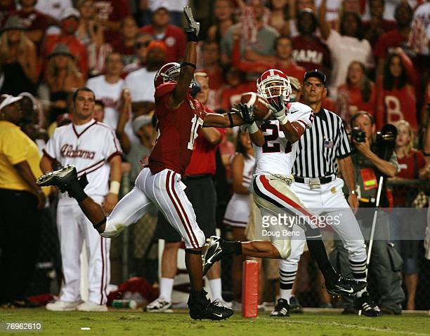 Split end Mikey Henderson of the Georgia Bulldogs catches the game winning touchdown in overtime over defensive back Lionel Mitchell of the Alabama...