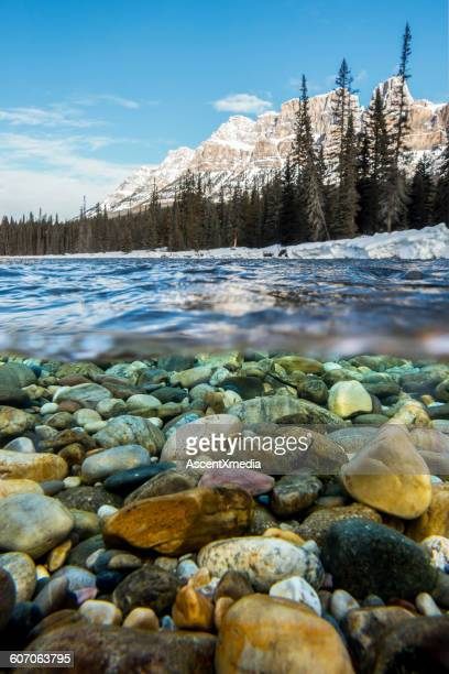 Split frame underwater view of river rocks and mtn