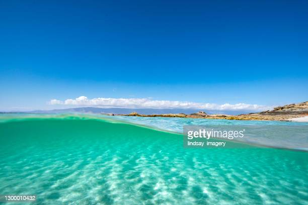 split image of clear blue ocean water with great clarity and blue sky - persian gulf countries stock pictures, royalty-free photos & images