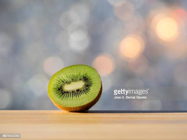 split kiwi fruit in half, illuminated by the light of the sun - fruta stock photos and pictures