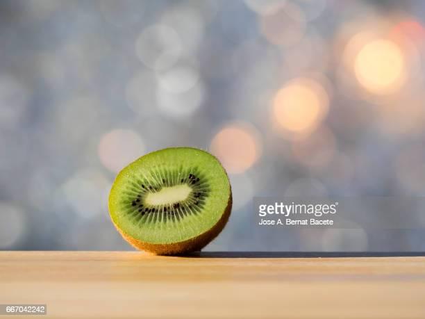Split kiwi fruit in half, illuminated by the light of the Sun