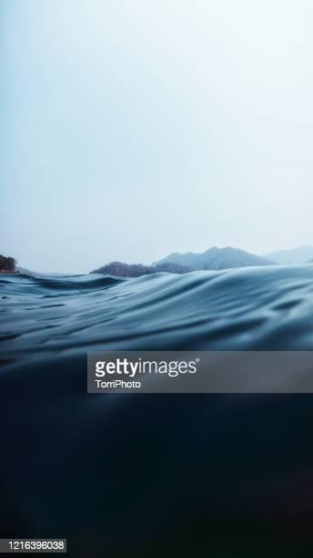 a split level of above and below the lake surface in deep blue water off the lakeshore wirh hills - unterwasseraufnahme stock-fotos und bilder