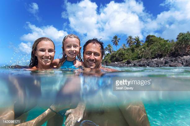 a split level view of a young family in the water at waimea bay. - waimea bay hawaii stock photos and pictures