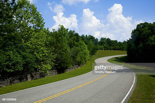 split rail fence and trees line a curve in road - timothy hearsum stock pictures, royalty-free photos & images