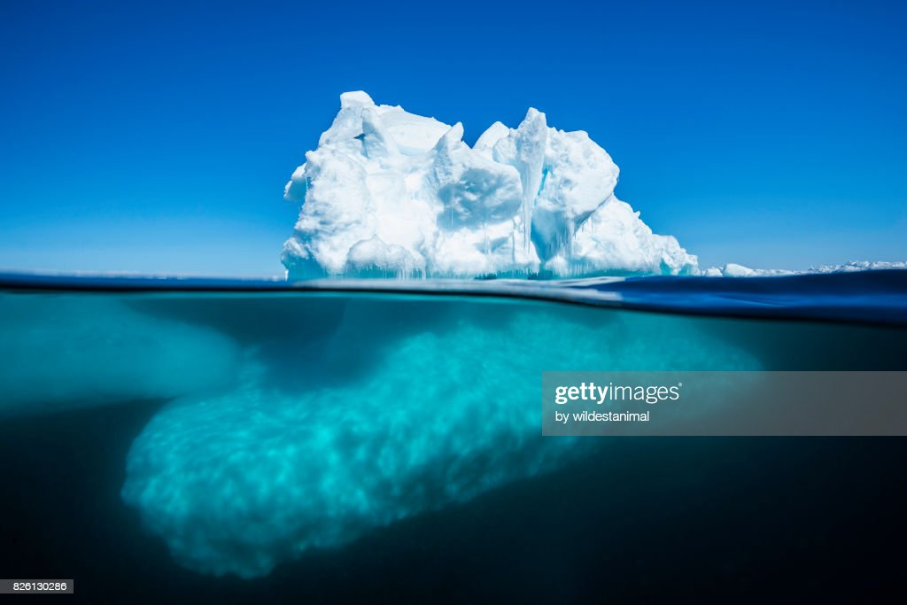 Split view of an iceberg at the ice floe edge showing what is above and below the waterline on a bright sunny summer's day in Admiralty Sound, Baffin Island, Canada. : Stock Photo