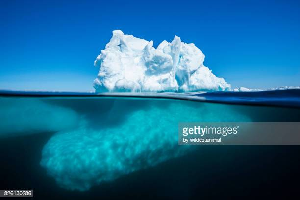 Split view of an iceberg at the ice floe edge showing what is above and below the waterline on a bright sunny summer's day in Admiralty Sound, Baffin Island, Canada.