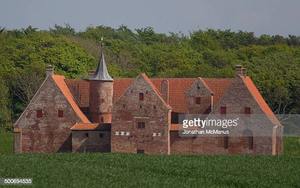 Spoettrup castle with filed in the foreground and a wooded bill behind it. The castle is medieval and is first mentioned in historical records in...