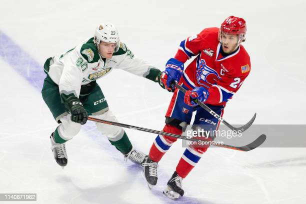 Spokane Chiefs defenseman Ty Smith follows through on a pass while being pressured by Everett Silvertips forward Robbie Holmes in the first period...