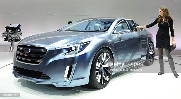 A spokesmodel closes the door of a 2015 Subaru Legacy Concept car displayed on November 20 2013 during media previews at the LA Auto Show in Los...