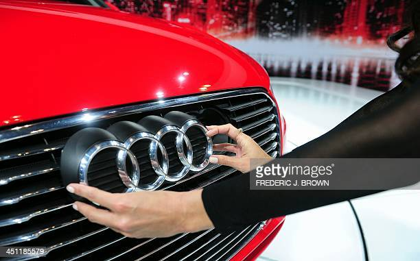 A spokesmodel moves the Audi logo on front grill to the left revealing the plug for the electric charger on the 2015 Audi A3 eTron displayed on...
