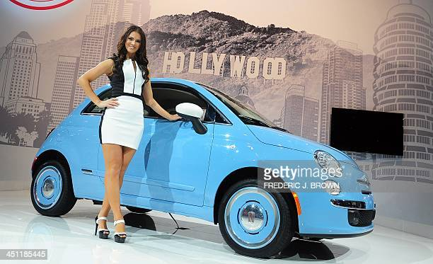 A spokesmodel poses beside the 2014 Fiat 500 1957 displayed on November 21 2013 at the LA Auto Show in Los Angeles California which opens to the...