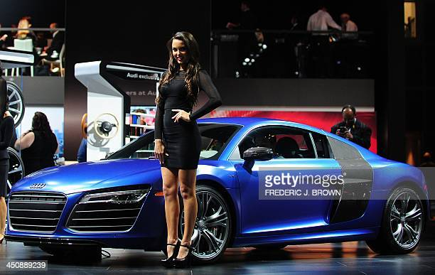 A spokesmodel poses beside the Audi R8 displayed on November 20 2013 during media previews at the LA Auto Show in Los Angeles California The LA Auto...