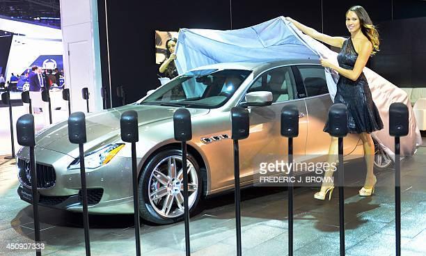 Spokesmodels cover up the 2014 Maserati Quattroporte Ermenegildo Zegna edition displayed on November 20 2013 during media previews at the LA Auto...