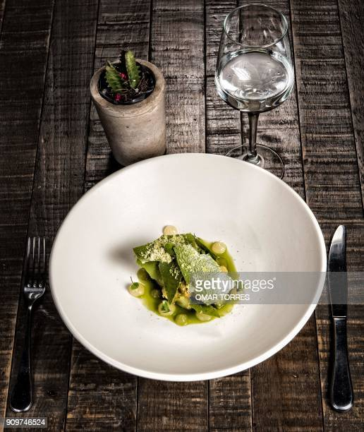A sponge cake with avocado oil macadamia nuts cold tomato soup broken pineapple cream avocado sorbet and matcha tea tiles cooked in oven is served at...