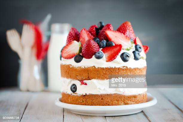 sponge cake with strawberries, blueberries and cream - dessert stock pictures, royalty-free photos & images