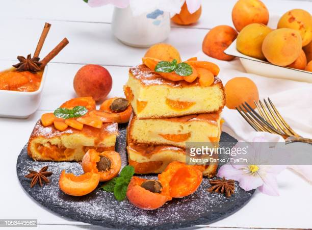 sponge cakes and apricots on slate over table - sponge cake stock pictures, royalty-free photos & images