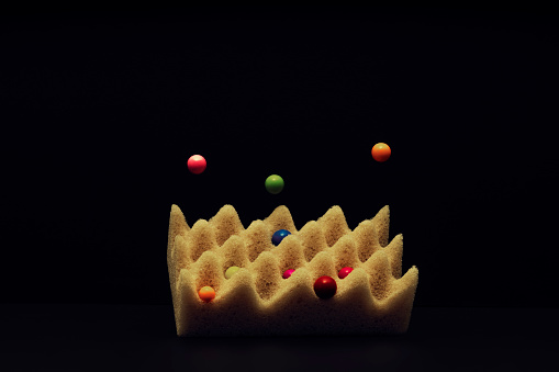 Sponge with marbles levitating and falling on it. - gettyimageskorea