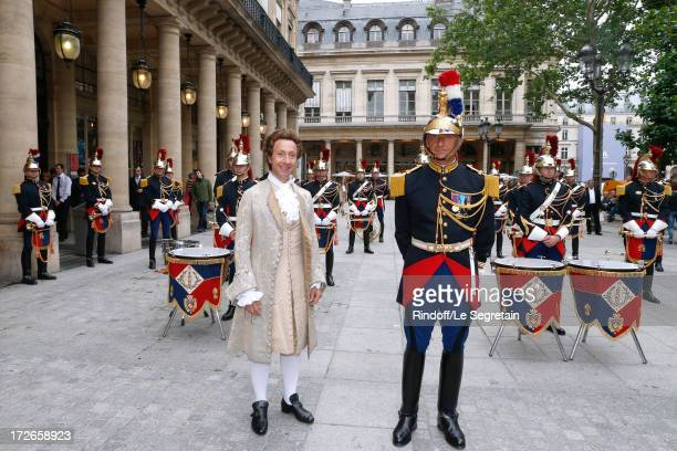 Sponsor of the evening Stephane Bern poses in front of the Orchestra of the French National Guard attends Le Grand Bal De La Comedie Francaise held...