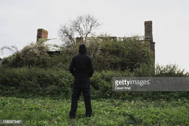 a spooky abandoned house, covered in vegetation. with a hooded figure standing in the countryside - hooded top stock pictures, royalty-free photos & images