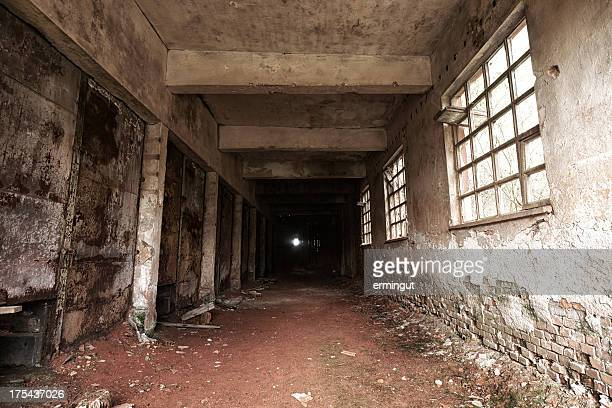 spooky corridor ending in darkness - dungeon stock photos and pictures
