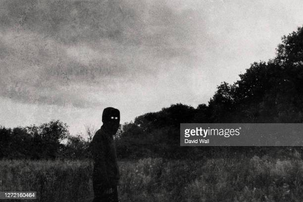 a spooky, demonic, hooded figure, with glowing eyes, looking at the camera. with a vintage, grainy, black and white edit. - magic eye stock pictures, royalty-free photos & images