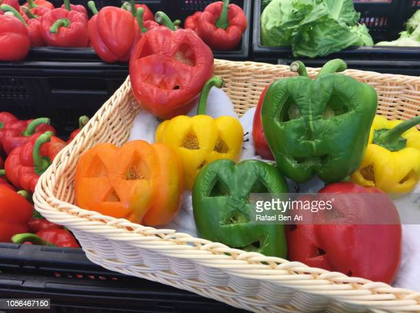 spooky faces curved on sweet peppers on halloween holiday - rafael ben ari stock-fotos und bilder