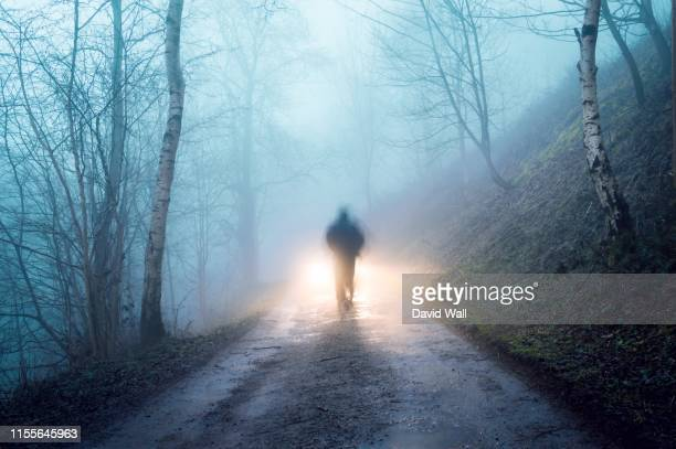 a spooky figure on forest track - ghost stock pictures, royalty-free photos & images