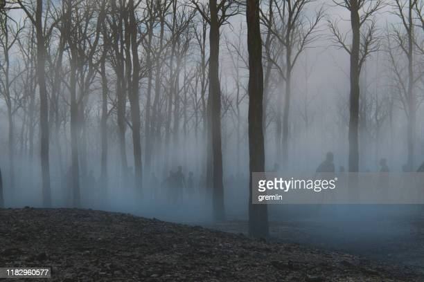 spooky foggy forest full of walking dead zombies - zombie stock pictures, royalty-free photos & images