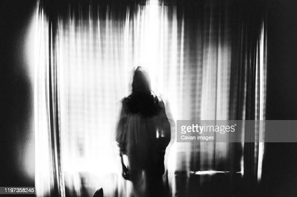 spooky image of ghost girl standing in window in eery light - aparición acontecimiento fotografías e imágenes de stock