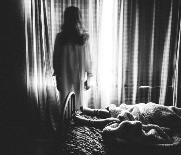 Spooky image of ghost girl staring at someone sleeping in bed