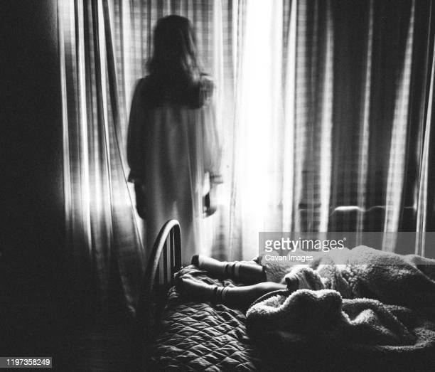 spooky image of ghost girl staring at someone sleeping in bed - goose bumps stock pictures, royalty-free photos & images