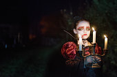 spooky little girl in halloween vampire costume with candles in the night