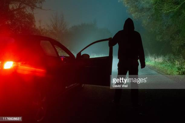 a spooky, mysterious hooded figure, standing next to a car with the door open. looking down a moody, foggy, road at night - crimine foto e immagini stock