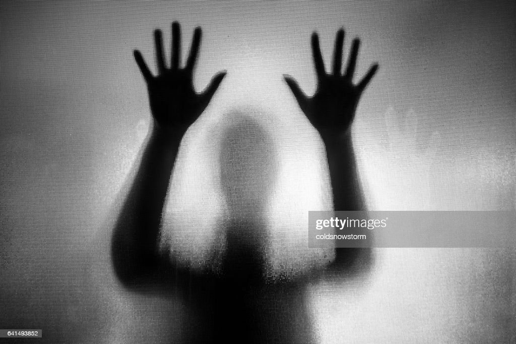 Spooky silhouette of woman with hands pressed against glass window : Stock Photo
