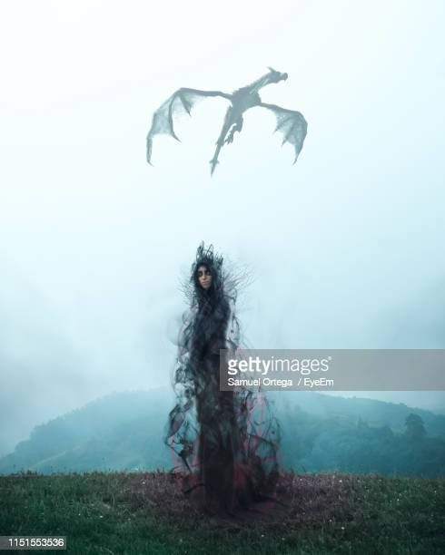 spooky woman standing on hill against dragon flying in sky - dragon stock pictures, royalty-free photos & images