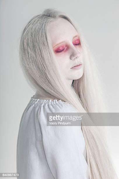 Spooky woman with closed red eyes and long hair against white background