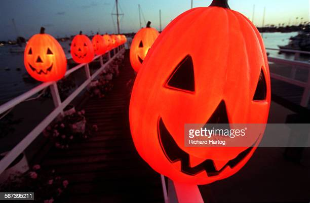 LSSpookyBalboa3RH––102698––As the sun sets behind them lit pumpkins line the dock in front of a house decked out for Halloween along South Bayfront...